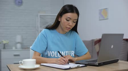 adolescente : Social worker writing list working laptop and smiling on camera, charity fund