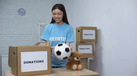 voluntário : Smiling volunteer putting clothes and toys in box, helping orphans, donation
