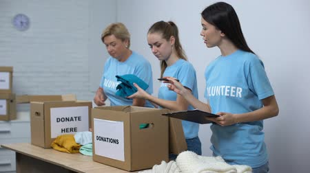 donate : Volunteers putting clothes in donation boxes, smiling social worker making notes