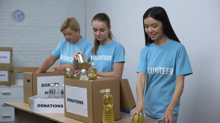 поддержка : Joyful women in volunteer t-shirts putting canned food boxes, provision donation