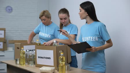 пожертвование : Social center workers preparing food donation boxes making notes, volunteering