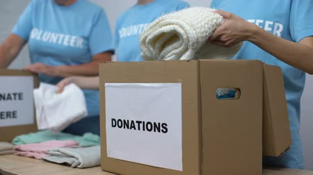 пожертвование : Social center volunteers putting clothes in donation boxes, altruism generosity Стоковые видеозаписи
