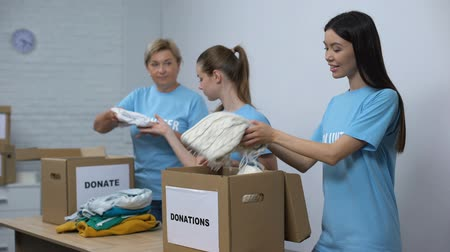 voluntário : Female social activist preparing donation boxes with clothes and smiling camera