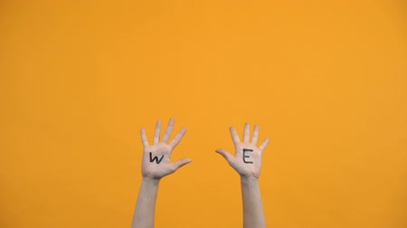 구성 : We written palms on orange background, volunteers raising hands, togetherness