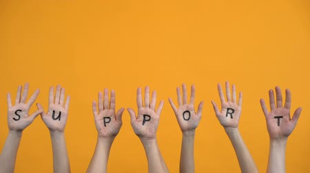 voluntário : Support written palms on orange background, teamwork cooperation, activists