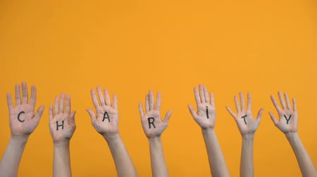 voluntário : Charity written palms on orange background, donation center, volunteer project