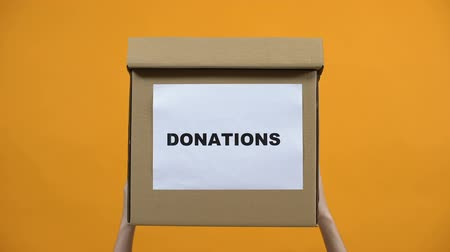 voluntário : Hands holding donation box on orange background, humanitarian aid, altruism