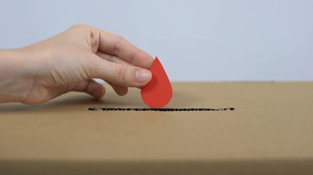 volontariat : Female hand putting red drop sign in cardboard box, blood donation center, help