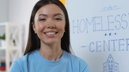 voluntary : Smiling young lady volunteer looking to camera in homeless support center, care Stock Footage