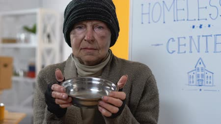voluntário : Depressed hungry homeless female demonstrating empty plate to camera, poverty Vídeos