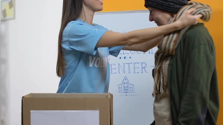 voluntário : Smiling lady volunteer giving warm clothes for homeless woman, support center
