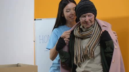 dankbaar : Young female volunteer giving winter coat for poor homeless smiling woman, aid