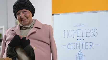 belongings : Poor homeless woman in donated warm clothing looking to camera in support center