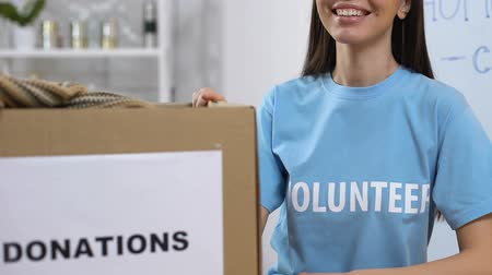 voluntário : Smiling volunteer standing near boxes with donated clothing, homeless assistance