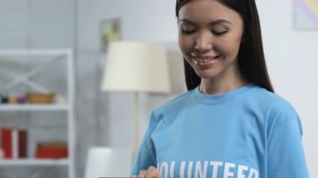 előléptetés : Female volunteer scrolling tab and smiling to cam, managing social network group