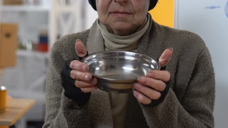 philanthropy : Poor unhappy homeless woman showing empty plate to camera, lack of funding Stock Footage