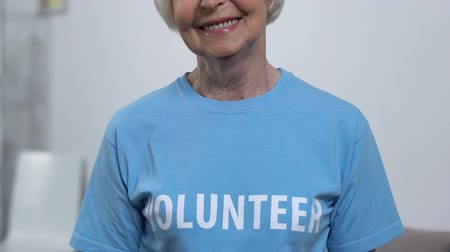 voluntário : Senior female volunteer looking to camera and smiling, active retired lady, aid Vídeos