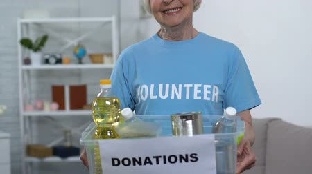 volontariat : Elderly lady volunteer holding box with food, looking to camera and smiling, aid Vidéos Libres De Droits
