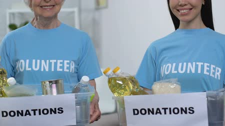 voluntary : Smiling young and senior female volunteers holding boxes with food, donations
