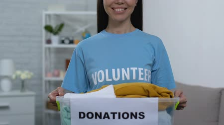 aparat : Openhearted young woman holding box with donated clothing, homeless care center Wideo