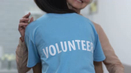voluntário : Female volunteer hugging smiling elderly lady in nursing home, care and support Vídeos