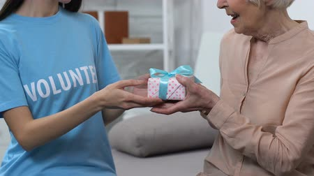 kapcsolat : Kind lady volunteer giving gift box for happy elderly woman, little surprise