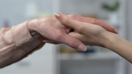 voluntário : Young and senior women holding hands, support and togetherness concept, care