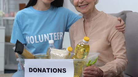 voluntário : Smiling young volunteer and aged female holding box with food, social help