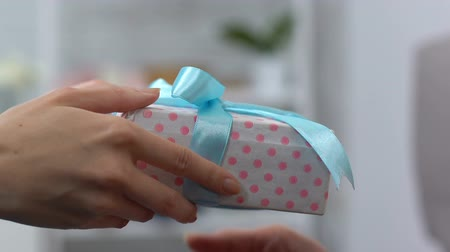 nagymama : Granddaughter giving present in box to grandma, celebrating birthday together Stock mozgókép