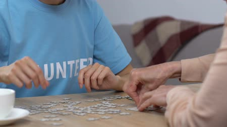csapatmunka : Young volunteer and senior woman doing puzzle in nursing home, leisure activity