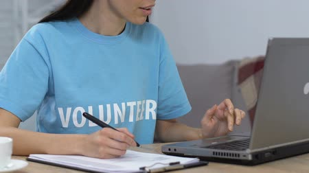 voluntário : Young lady volunteer working on laptop and making to do list, planning budget