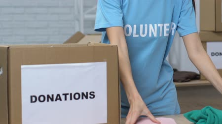 판지 : Female volunteer putting clothes in box for donations, charity organization