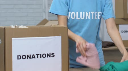 солидарность : Young lady volunteer packing belongings in box for donations, poor people care
