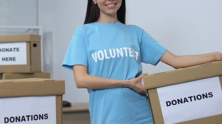 солидарность : Openhearted female volunteer holding donation box and smiling to camera, care Стоковые видеозаписи
