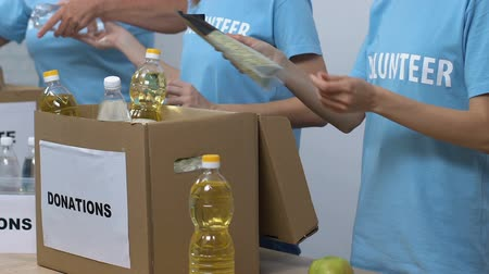 voluntary : Group of volunteers packing food in donation boxes, working in social center Stock Footage