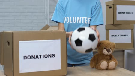 belongings : Lady volunteer putting children things in box, smiling to cam, helping orphanage