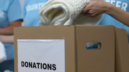 voluntário : Volunteers packing clothes in box for donations, low-income families assistance