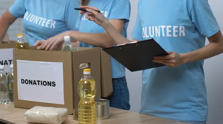 солидарность : Volunteers putting groceries in boxes while supervisor checking list, donations Стоковые видеозаписи