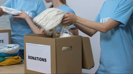 pudełko : Group of volunteers packing clothing in boxes, friendly lady smiling to camera