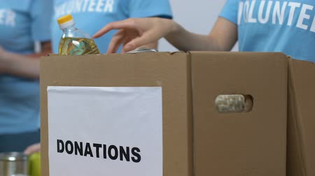 организации : Group of volunteers putting groceries in donations box, charity organization Стоковые видеозаписи