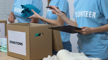 voluntário : Volunteers packing donated clothes in boxes, supervisor holding check list, care