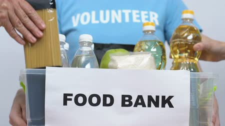 voluntary : Group of volunteers packing food in donation box, charity concept, togetherness Stock Footage