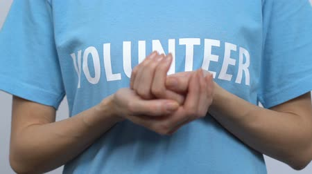 voluntary : Female volunteer holding red paper drop and showing to camera, blood donation Stock Footage