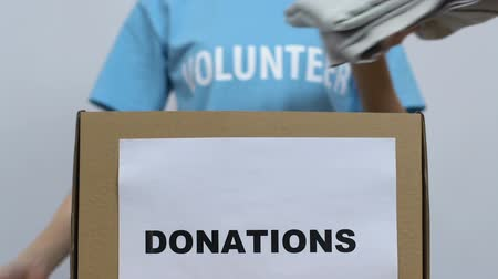 belongings : Lady volunteer packing clothes in box, orphanage charity organization, donations