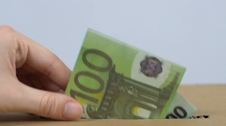 assistência : Volunteer hand throwing euro banknote in box, donating money to charity, aid