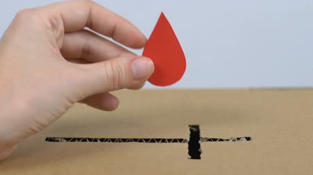 salva vidas : Hand putting paper drop in cardboard box with cross shaped hole, blood donation Vídeos