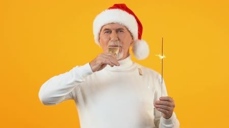 очки : Celebrating mature man santa hat drinking champagne from glass holding sparkler