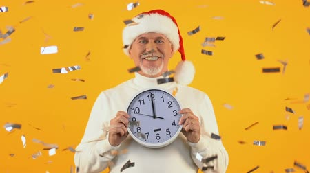 szenteste : Happy aged man in santa hat holding clock showing midnight, New Year party