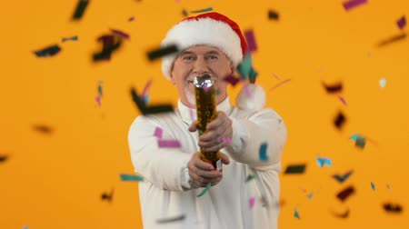 празднование : Senior male blowing up confetti firecracker orange background, party decoration