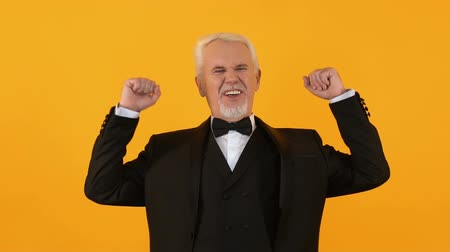 happiness symbol : Joyful aged man showing yes gesture on bright background, success achievement